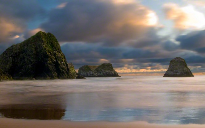 The Crescent Beach along the Oregon coastline with dark clouds in the sky.