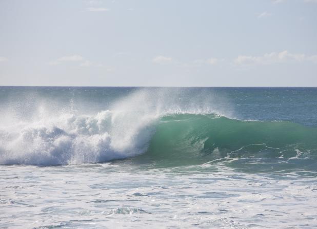 An ocean wave near Hawaii crashes and creates mist with a blue, clear sky above.