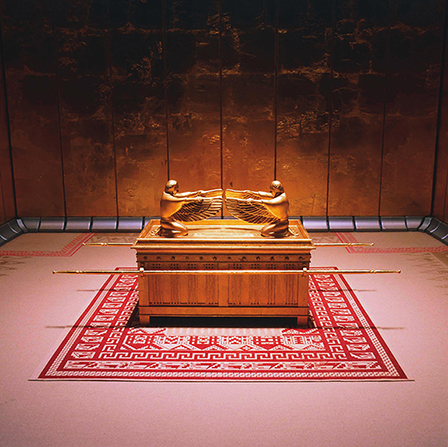 A replica of the ark of the covenant, covered in gold, standing on a woven red and white rug.