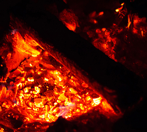 A photograph of red embers glowing in a fire pit on a dark night.
