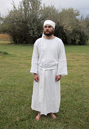 A model standing in a grassy field, wearing the plain white clothing of an Old Testament priest.