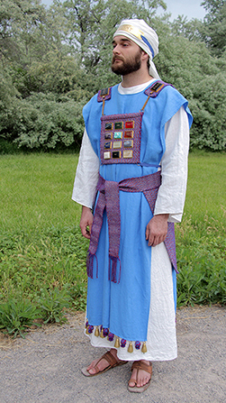 A model standing outside, wearing the colorful blue and purple clothing of an Old Testament high priest.