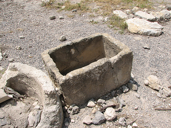 A  small, crumbling stone container historically used for animal feed.