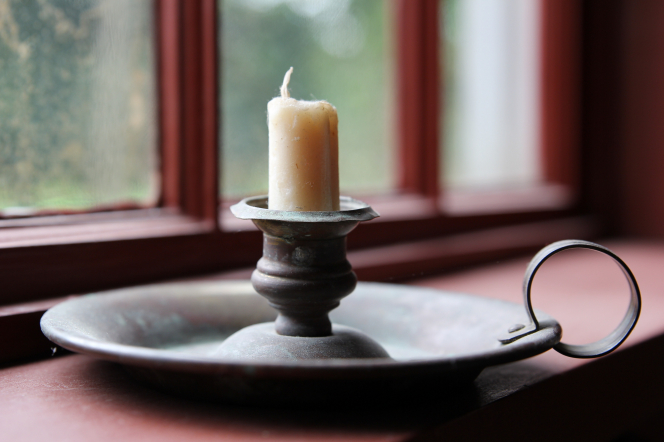A white wax candle, nearly used up, in a candle holder on a windowsill.