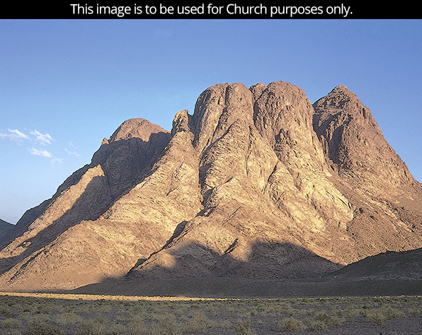 A photograph of a mountain thought to be Mount Sinai, rising above a desert landscape on a clear day.