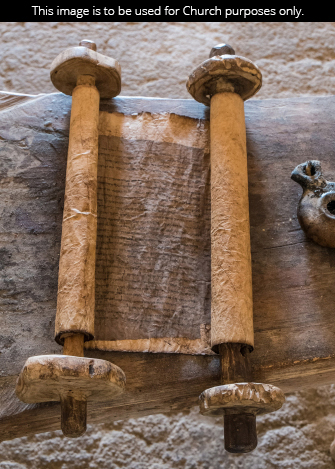 A scroll of worn parchment lying on a crude table.