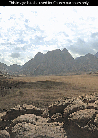 A photograph of the Sinai wilderness during the day, with Mount Sinai in the background and clouds overhead.