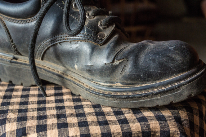 A dirty and worn black shoe on a checkered towel.