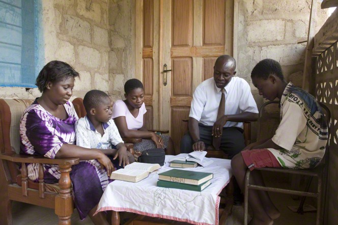 A family sitting in a circle around a table to read scriptures and sing hymns.