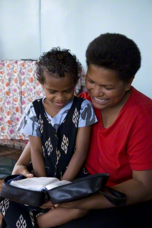 A daughter sits on her mother's lap and reads the scriptures with her.