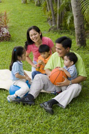 A mother and father sit on a lawn with their three children and play with a basketball.