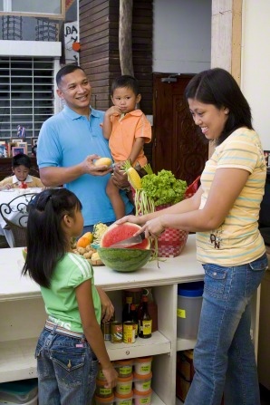 A mother and father cut up fruit in the kitchen while talking with their young children.