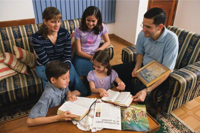 A family sitting in a living room with a Church magazine and the scriptures open for family home evening.