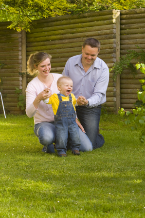 A mother and father kneel on the grass and help their baby boy walk.
