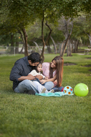 A mother, father, and daughter sit in the park with toys and a blanket.