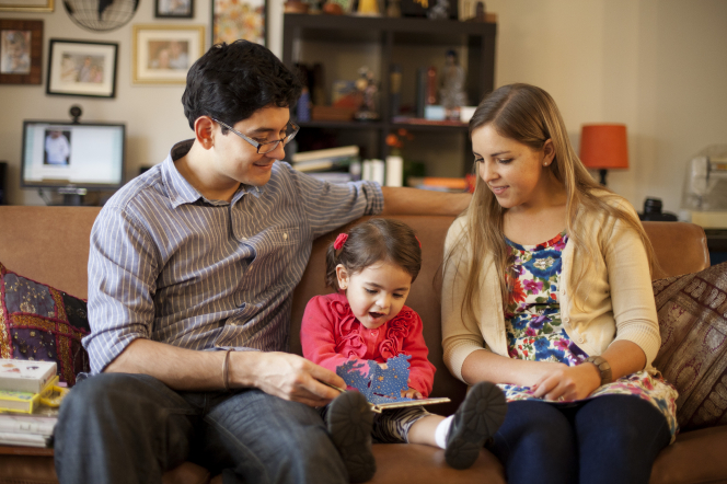 A mother and father sit on a couch together with their toddler daughter and read a book to her.
