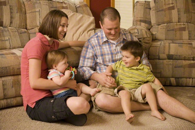 A mother and father sit with their two children on the living room floor.