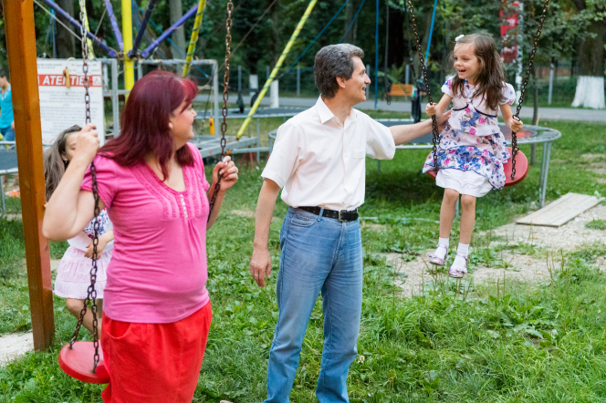 A mother and father in Moldova play on a swing set together with their two daughters.