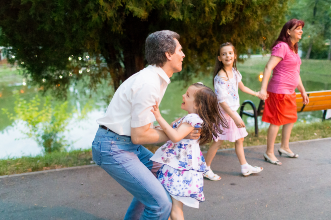 A father lifts his daughter into the air while the mother and their other daughter walk nearby in a park.