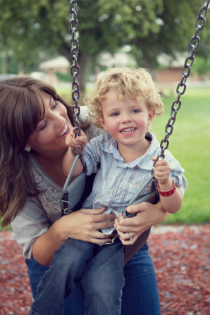 A mother pushes her son on a swing at the park.