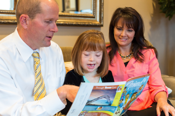 A mother and father sit and read the Friend magazine with their daughter, who has Down syndrome.