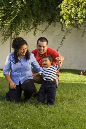 A mother and father kneel in the grass while they help their baby son walk.