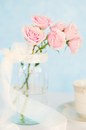 Pink roses in a jar with a ribbon tied around it on a table.