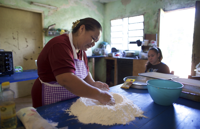 A woman making bread at a table with a young woman sitting nearby.