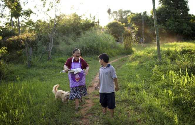A woman with fresh baked bread is walking with her grandson.