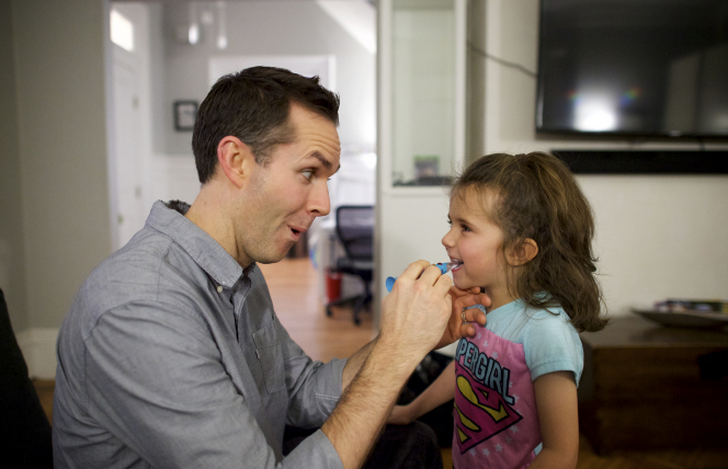 A father brushes his daughter's teeth.