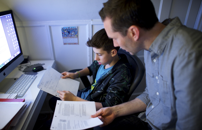 A father helps his son with his homework.
