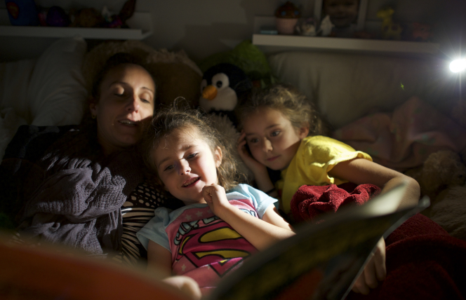 A mother reads with her daughters at night in bed.