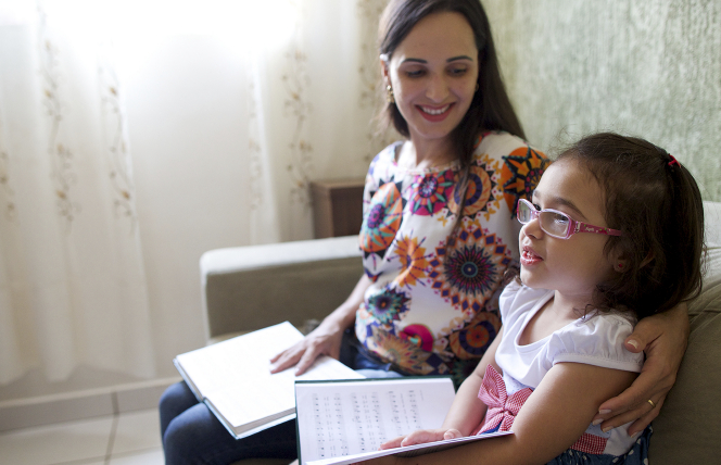 A mother and daughter holding hymn books.