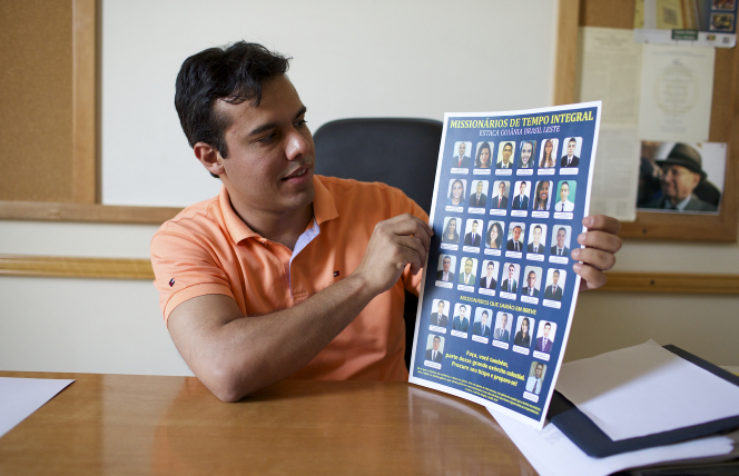 A man holding up chart of missionaries.