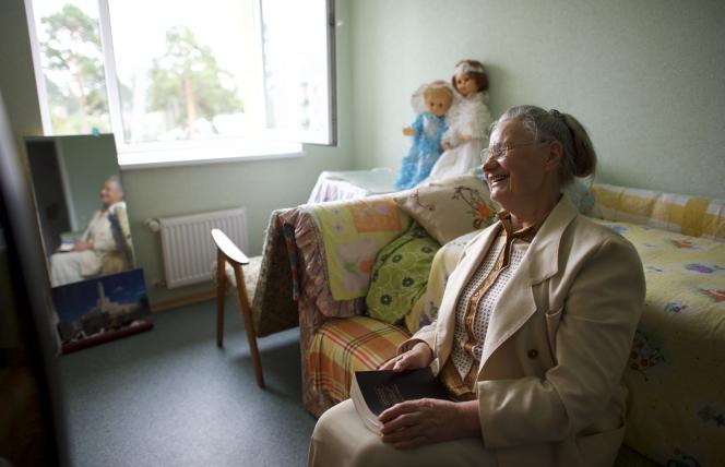 An elderly woman holding a Book of Mormon.