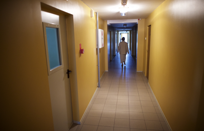 An elderly woman walking down the hall of a meetinghouse.
