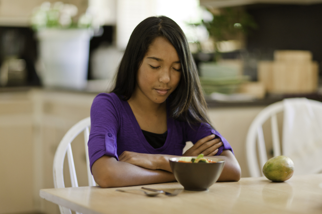 A young girl folds her arms and prays while sitting at a dinner table, about to eat.
