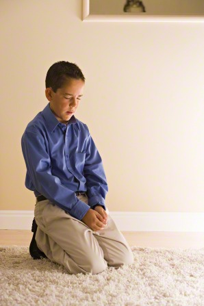 A boy kneels on a rug, clasps his hands, and prays.