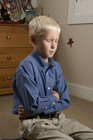 A young boy kneels down, folds his arms, and closes his eyes while saying a prayer in his bedroom.