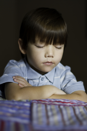 A young boy folds his arms, closes his eyes, and prays by his bed.