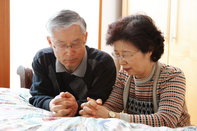 An elderly couple kneeling by their bed to pray together.