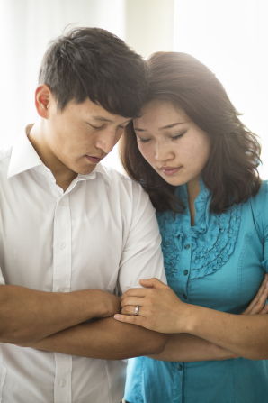 A young couple fold their arms and lean their heads together while they pray.