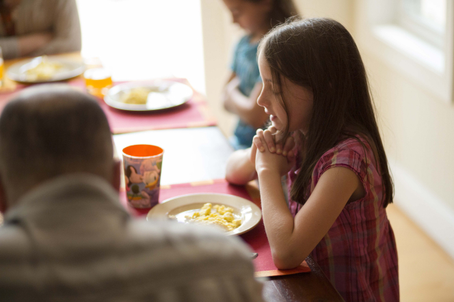 A little girl clasps her hands and leads her family in prayer before they eat dinner at the table.