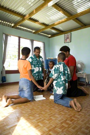 A family in Fiji hold hands in a circle while the father leads them in prayer during scripture study in their living room.