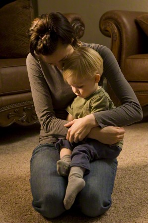 A mother kneels down with her son on her lap and wraps her arms around him while they both bow their heads and pray in a living room.