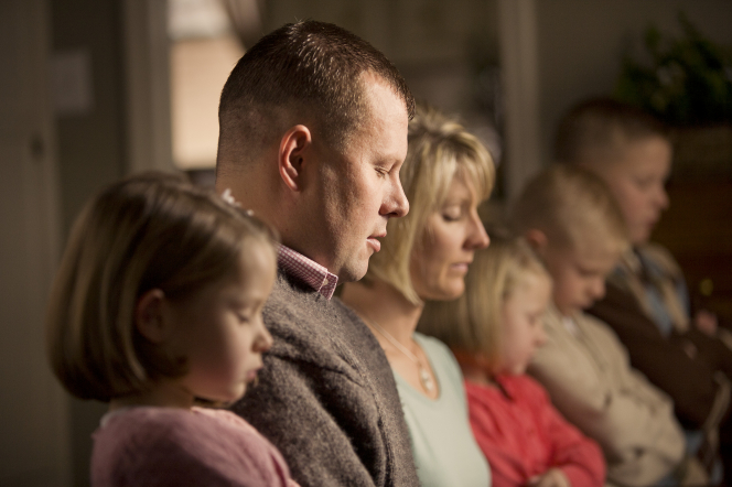 A family kneel in a row while the father closes his eyes and prays.