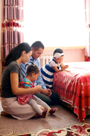 A family kneel in a bedroom next to a bed and pray together.