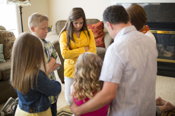 A mother and father kneel down with their four children in their living room and pray together.