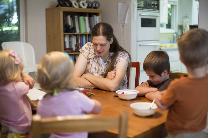 A mother folds her arms and prays at the breakfast table with her four children.