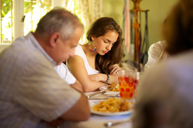 A teenage girl at the dinner table bows her head, folds her arms, and prays while the rest of the family sit around the table with their heads bowed.